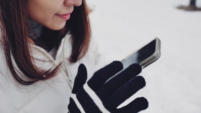 北海道の電話で雪の山の写真を撮るアジアの観光客。 - glove点の映像素材/bロール