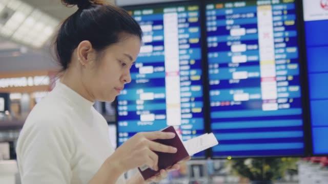 asiatisk turist kvinna kontrol lera och titta flygning vid ankomst avgång board - visa bildbanksvideor och videomaterial från bakom kulisserna