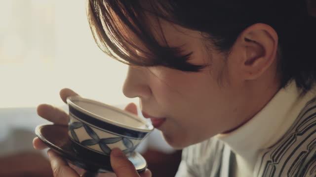 vídeos y material grabado en eventos de stock de mujer turista asiática bebiendo té caliente en casa de campo en japón - taza de té