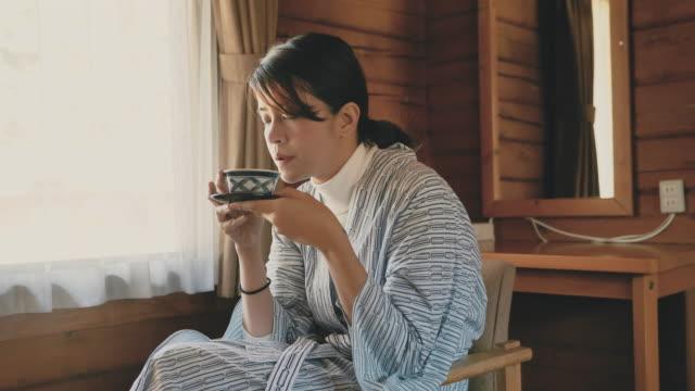 日本のコテージで熱いお茶を飲むアジアの観光客の女性 - くつろぐ点の映像素材/bロール