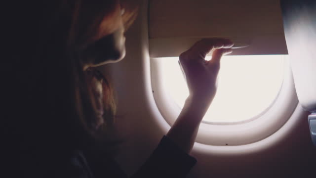 asian tourist woman open the window on airplane - abitacolo video stock e b–roll