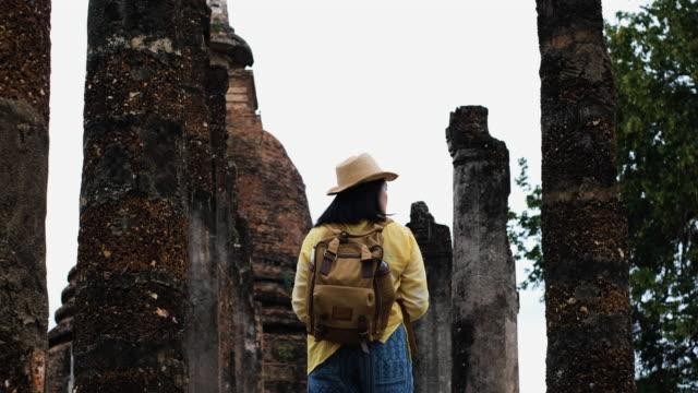asiatische touristen-frau sightseeing in alten tempel thai architektur in sukhothai,thailand. weibliche reisende in lässigen thai tücher stil besuch stadtkonzept - hut stock-videos und b-roll-filmmaterial
