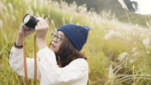 アジア観光客の女性に彼女のカメラで山の写真を撮る - カメラ点の映像素材/bロール