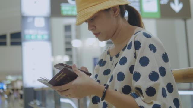 空港で携帯電話を使用してアジアの観光客の女性。 - パスポート点の映像素材/bロール