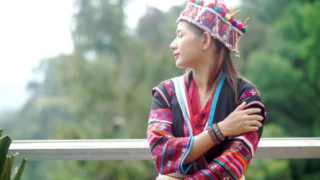 アジアの観光客の女性は、アカ族をドレスアップし、山の背景を持つ木製のテラスで楽しんでいます。 - 丘点の映像素材/bロール