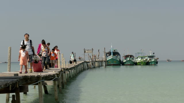 Asian tourists arrive at wooden jetty