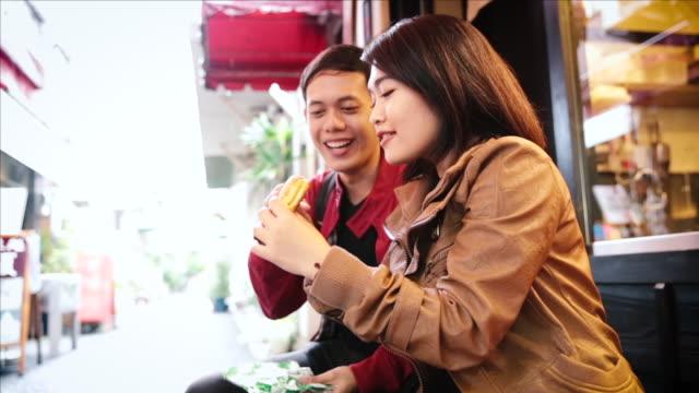 stockvideo's en b-roll-footage met asian tourists eating japanese traditional food on the street in tokyo - verwonderingsdrang