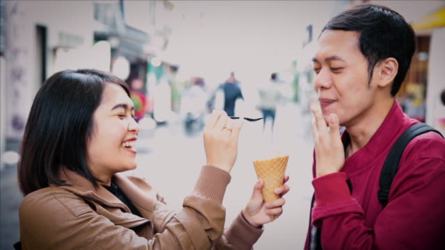 asian tourists eating matcha soft ice cream on the street in tokyo - green tea ice cream stock videos and b-roll footage