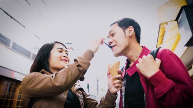 stockvideo's en b-roll-footage met asian tourists eating matcha soft ice cream on the street in tokyo - verwonderingsdrang