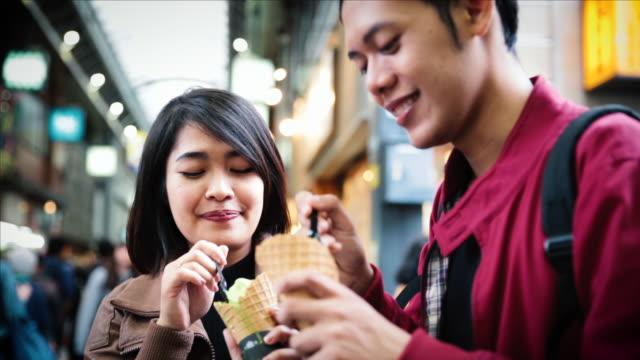 asian tourists eating matcha soft ice cream on the street in tokyo - アイスクリーム点の映像素材/bロール