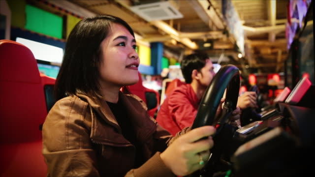 stockvideo's en b-roll-footage met asian tourists plaiying a racing machine game in tokyo - verwonderingsdrang