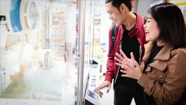 stockvideo's en b-roll-footage met asian tourists playing an arcade game in tokyo - verwonderingsdrang