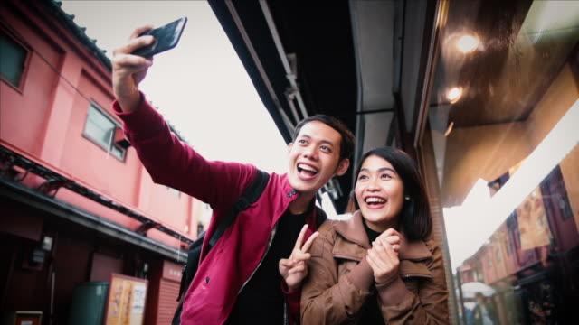 stockvideo's en b-roll-footage met asian tourists taking a selfie on the street in tokyo - verwonderingsdrang