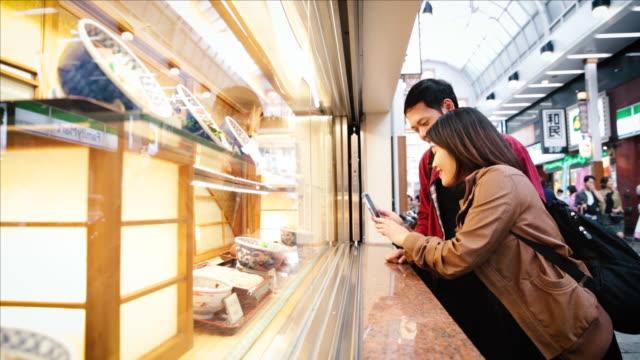 stockvideo's en b-roll-footage met asian tourists watching displays of the japanese restaurant on the street in tokyo - verwonderingsdrang