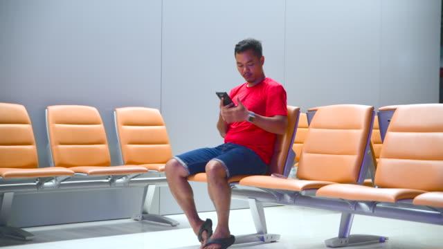 asiatische reisende mittels mobiltelefon während flugzeug flug warten - nur junge männer stock-videos und b-roll-filmmaterial