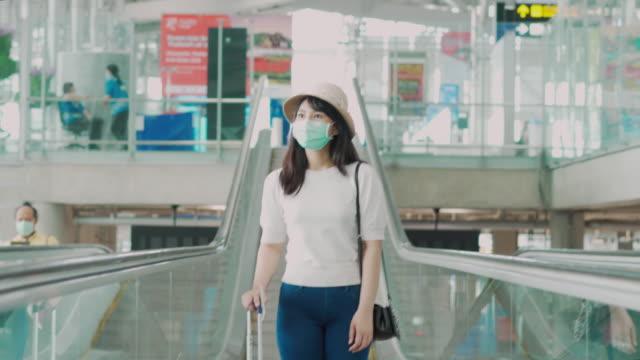 エスカレーターに立って空港のターミナルの外を見てフェイスマスクを身に着けている荷物を持つアジアの旅行者の女性は、旅のためにゲートに行きます。新しい通常の旅行コンセプト。 - passenger点の映像素材/bロール