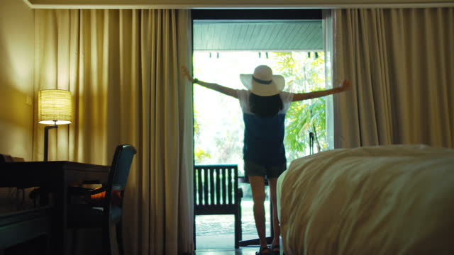 asian traveller women are staying in a hotel room.open the curtain and  door in the room looking to outside view.travel in holidays concept.4k slow motion. - hotel stock videos & royalty-free footage