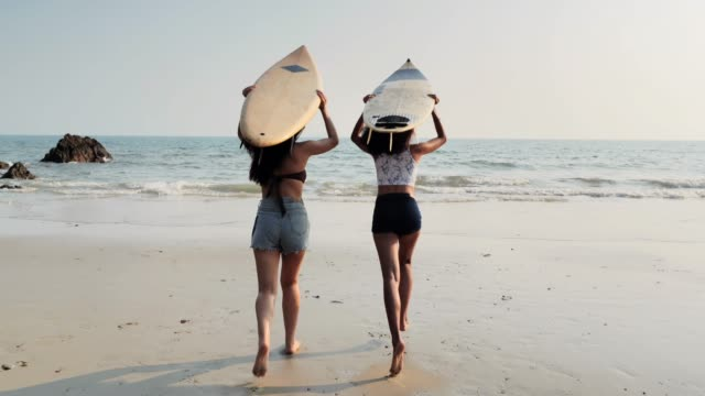 asian two beautiful young women surfer girls in bikinis with white surfboards at a beach.sports cinemagraphs - piacere video stock e b–roll