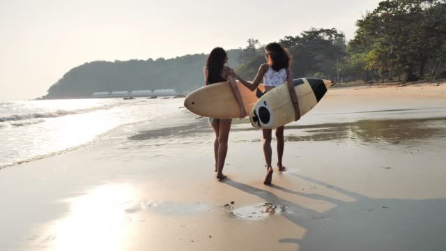 asian two beautiful young women surfer girls in bikinis with white surfboards at a beach.sports cinemagraphs - sport video stock e b–roll