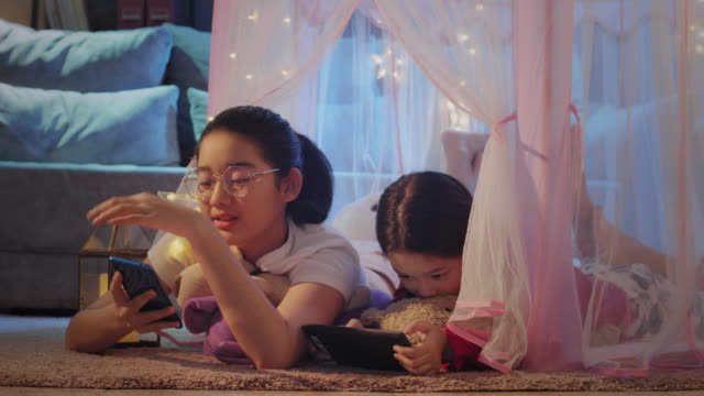asian two sister have fun in camping tent at home and watching digital tablet and smart phone in the living room at home. sibling lying on the floor inside a cute tent and enjoy playing social media on tablet and mobile phone with coronavirus quarantine. - fortress stock videos & royalty-free footage