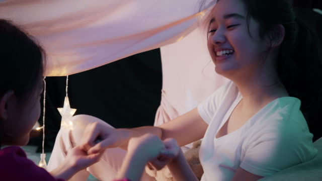 asian two sister have fun playing in camping tent in the living room at home. sibling sitting on the floor in side a cute tent. they are playing clapping their hand. stay home from coronavirus quarantine. - sister stock videos & royalty-free footage