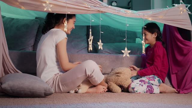 asian två syster ha kul att leka i campingtält i vardagsrummet hemma. syskon sitter på golvet i sidan en söt tält. de spelar klappar sin hand. stanna hemma från coronavirus karantän. - fort bildbanksvideor och videomaterial från bakom kulisserna