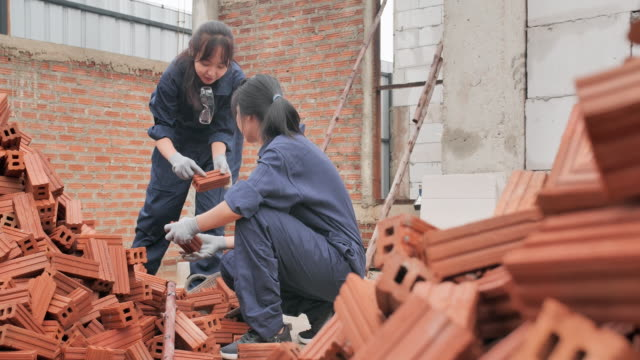 asian two teenager girl of volunteer working construction of a housing project together.teen activism - altruism stock videos & royalty-free footage