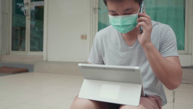 asian unemployed man wear face mask look stressed, try to finding a job on smart phone and tablet because of virus issues covid-19 at home. - unemployment benefit stock videos & royalty-free footage