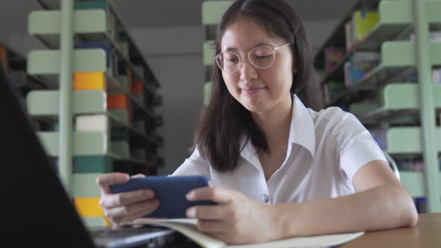 Asian university student girl reading book and working and online shopping with laptop and smart phone do her homework in public in public library