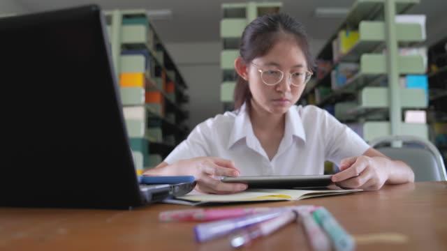 アジアの大学生の女の子の読書の本とノートパソコンとスマートフォンでの作業公共図書館で公共の中で彼女の宿題をする - 日本の学生服点の映像素材/bロール