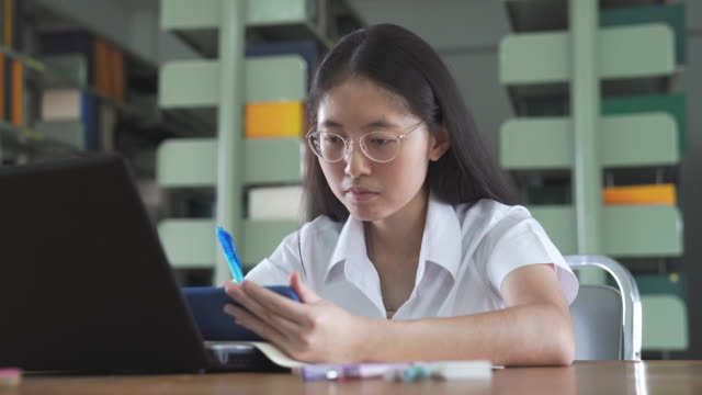 Asian university student girl reading book and working with laptop and smart phone do her homework in public in public library