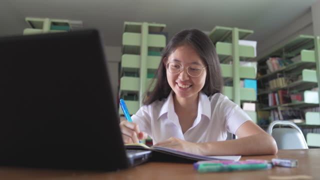 asiatiska universitets student flicka läsa bok och arbeta med laptop och smart telefon göra sina läxor offentligt i offentliga bibliotek - uniform bildbanksvideor och videomaterial från bakom kulisserna