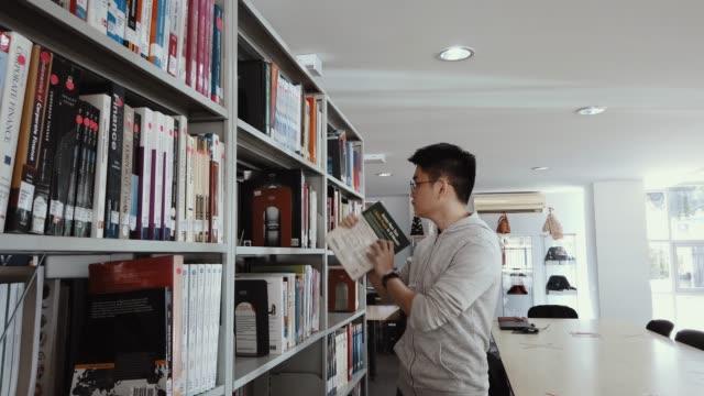 vídeos y material grabado en eventos de stock de estudiante universitario asiático que estudia en la biblioteca en busca de libros - decoración objeto