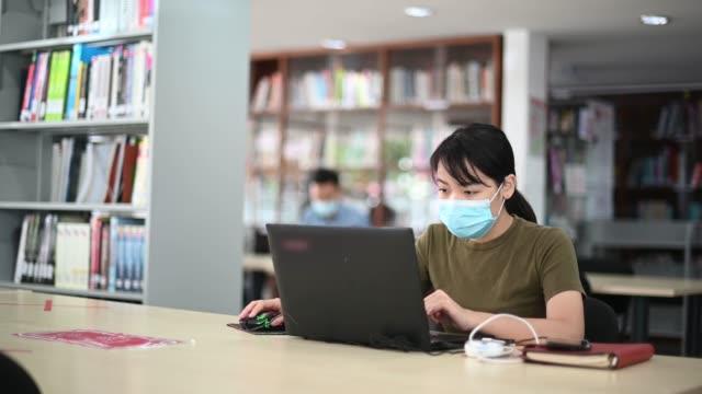 asiatiska universitetsstudent studerar i biblioteket observera sociala avståndstagande - campus bildbanksvideor och videomaterial från bakom kulisserna