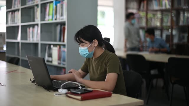 社会の離散を観察する図書館で勉強しているアジアの大学生 - 公共図書館点の映像素材/bロール