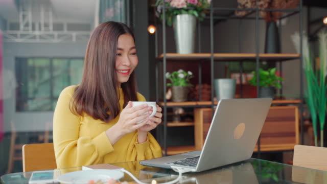 自宅で仕事や自宅のビジネスチームとのオンラインインターネット通信での仕事にラップトップを使用してアジア人、 - 職探し点の映像素材/bロール