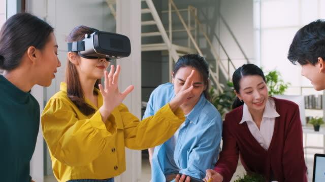asian ux developer and ui designer examining virtual reality eyewear with mobile app prototype design at modern office.creative digital development agency.tilt up - design professional stock videos & royalty-free footage
