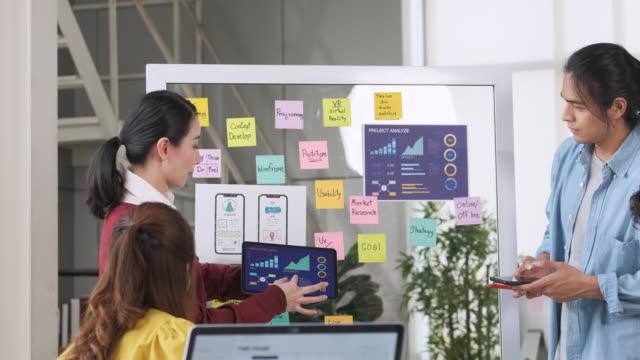 アジアの ux 開発者と ui デザイナーは、現代オフィスでの会議でホワイトボード上のモバイル アプリ インターフェイスデザインを提示し、テストします。クリエイティブデジタル開発モバイ - プロトタイプ点の映像素材/bロール