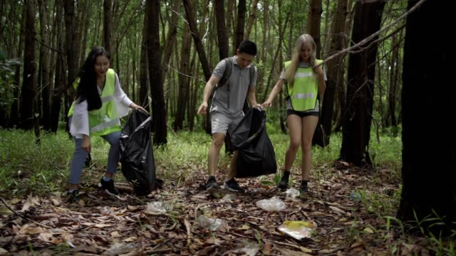asian volunteer group collects garbage in parks. - altruism stock videos & royalty-free footage