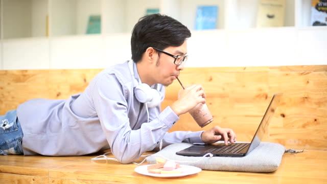 ms - アジア人のホワイト カラー労働者彼の飲み物を楽しみながらのラップトップに取り組んで - white collar worker点の映像素材/bロール