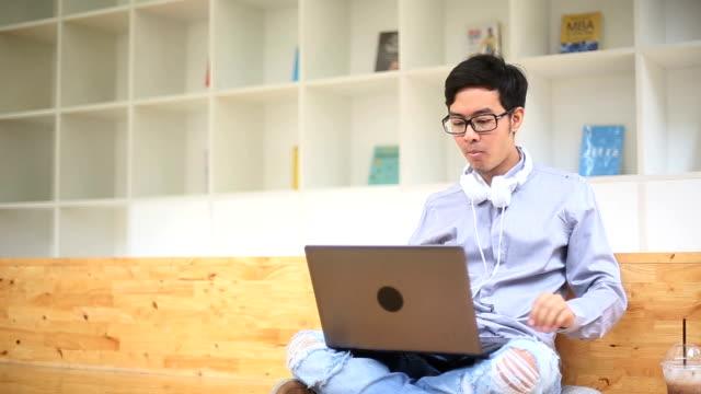 彼のおやつを楽しみながらのラップトップに取り組んでアジア人のホワイト カラー労働者 - white collar worker点の映像素材/bロール