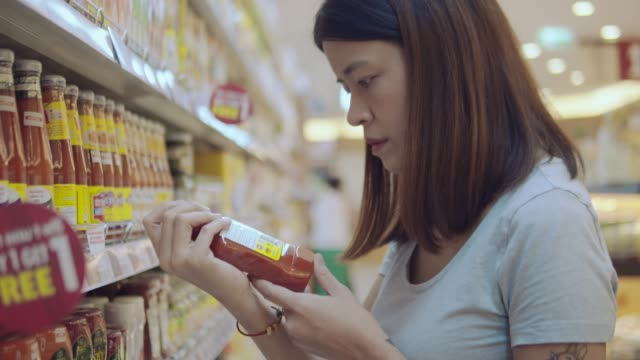 asian wife in grocery store - packet stock videos & royalty-free footage