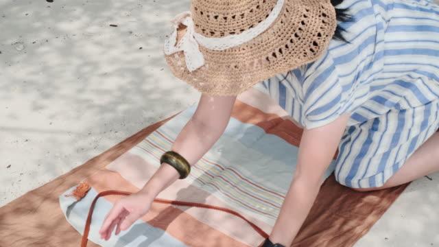 vídeos de stock, filmes e b-roll de asiática mulher alinhamento cobertor piquenique na praia.relax férias de verão - toalha de praia