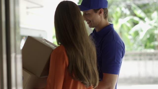 stockvideo's en b-roll-footage met aziatische vrouw en bezorger die geeft haar kartonnen doos postpakket - mid volwassen mannen