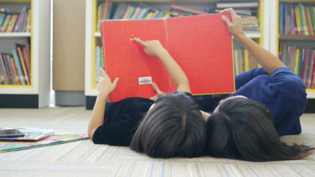 asian woman and girl reading book in library - child care stock videos & royalty-free footage