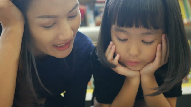 asian woman and girl reading book in library - parent stock videos & royalty-free footage