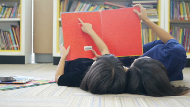 asian woman and girl reading book in library - saggezza video stock e b–roll