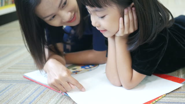 図書館で本のアジア女性と読んでいる女の子 - 小学校点の映像素材/bロール