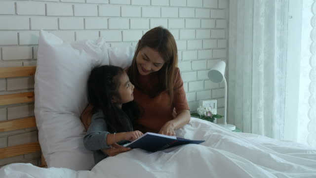 Asian woman and girl reading book on bed