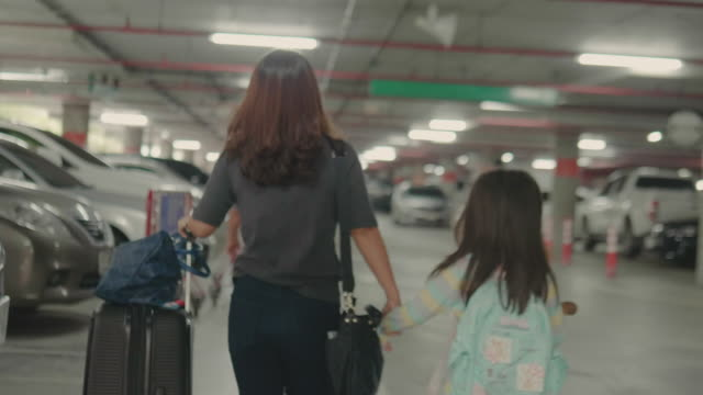 Asian woman and girl with suitcase at car park.